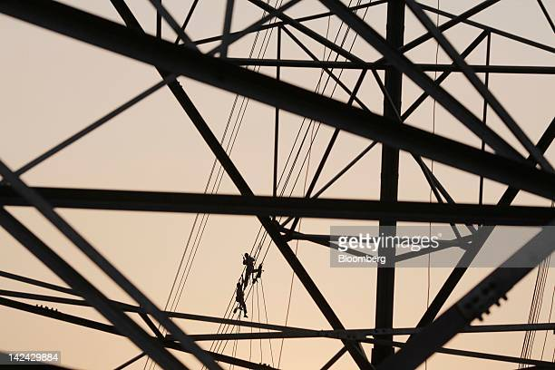 Men work on power transmission lines in Tezpur India on Thursday March 29 2012 Prime Minister Manmohan Singh's government plans to attract $1...