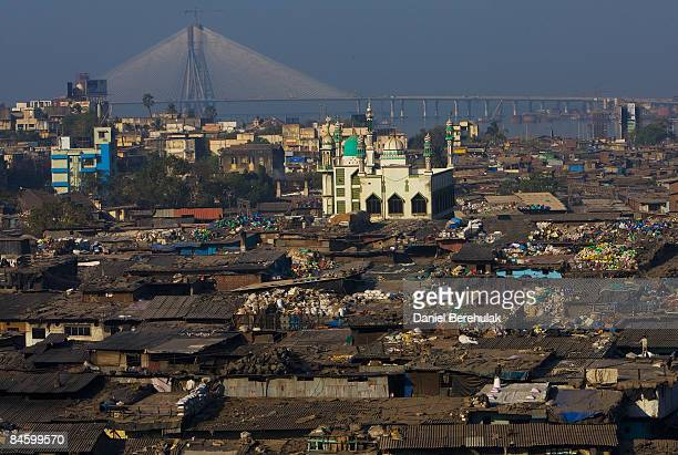 Men work on rooftops to recycle waste in the Dharavi slum on February 3 2009 in Mumbai India The redevelopment of the Jari Mari slum situated near...