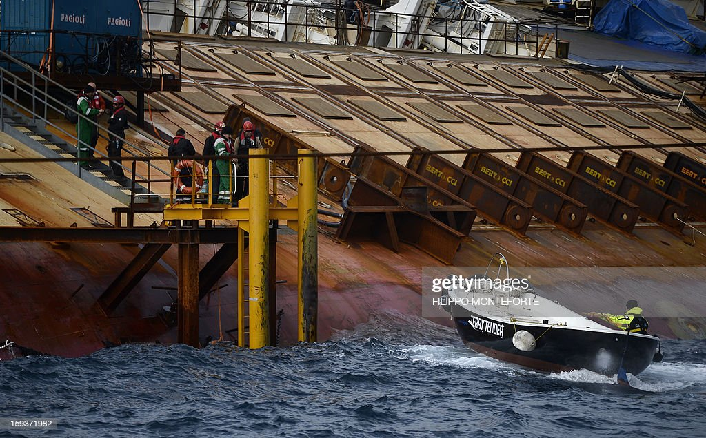 Men work on the Costa Concordia cruise ship laying aground outside the port the western Italian island of Giglio on January 12, 2013. A year after the Costa Concordia tragedy in which 32 people lost their lives, the giant cruise ship still lies keeled over on an Italian island and its captain Francesco Schettino has become a global figure of mockery.