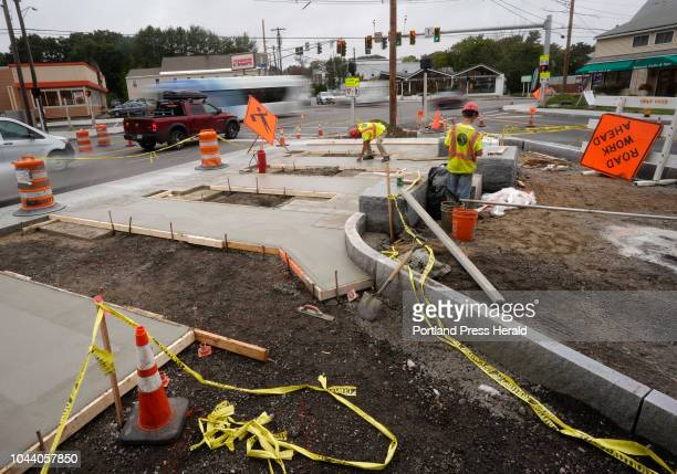 Men work on the new plaza at Woodfords Corner on Wednesday September 26 2018 Installation of a light sculpture at the plaza should happen in the next...