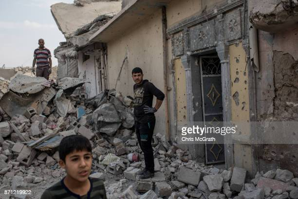 Men work to clear rubble from their house in an outer neighborhood of the Old City in West Mosul on November 6 2017 in Mosul Iraq Five months after...