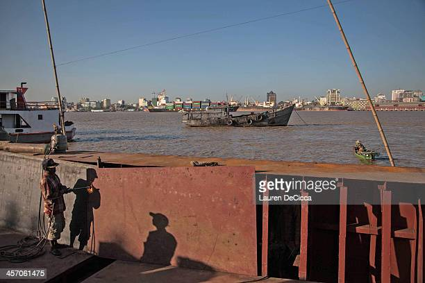 Men work to repair a cargo ship on the banks of the Irrawaddy River on December 16 2013 in Yangon Myanmar Large cargo ships on the Irrawaddy River in...