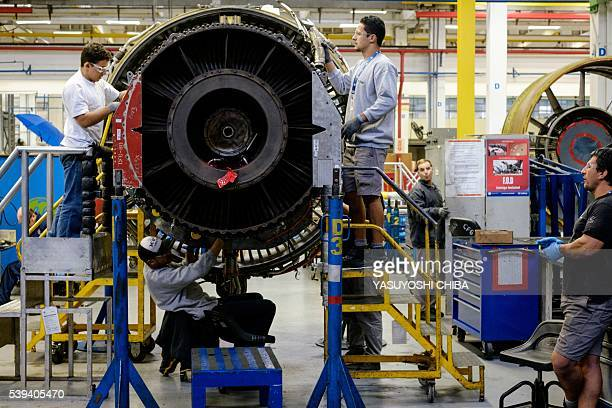 Men work with a jet engine at General Electric Celma, GE's aviation engine overhaul facility in Petropolis, Rio de Janeiro, Brazil on June 8, 2016. /...