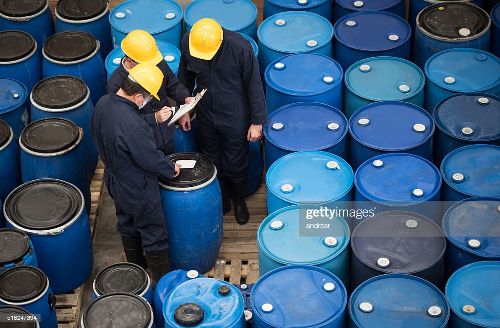 Men working at a chemical warehouse : Stock Photo