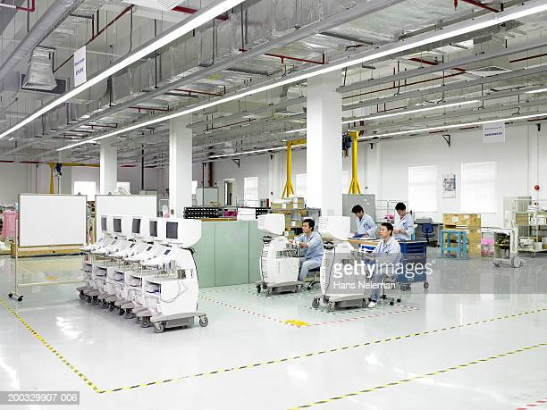 Men working at computers in medical manufacturing plant