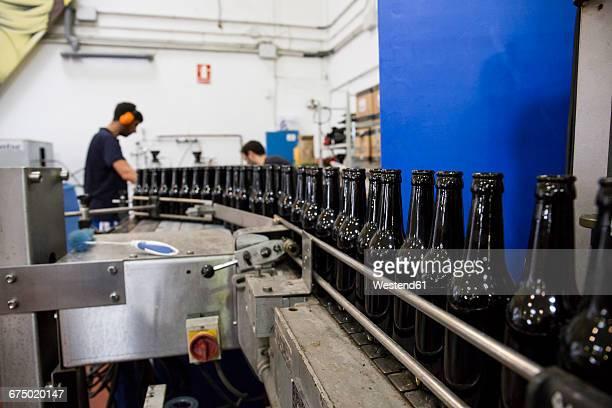 Men working in beer bottling plant