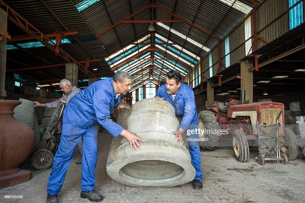 Men working in industrial pot factory : Stock Photo