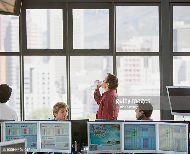 men working in office, on drinking water from bottle - börsenhändler stock-fotos und bilder