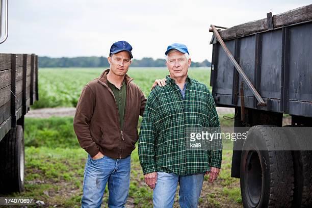 Homens a trabalhar numa quinta de batata, camiões