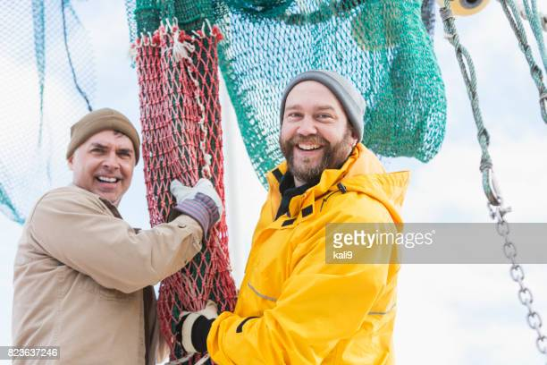 Men working on commercial fishing boat preparing nets
