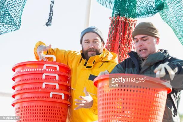 Men working on commercial shrimp boat unloading basket
