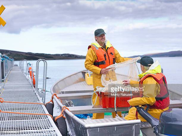 Men working on fishing boat in Scottish salmon farm on loch