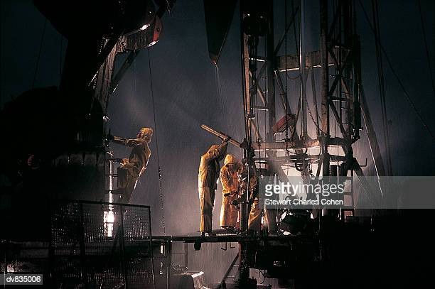 men working on oil rig in the rain - oil worker stock pictures, royalty-free photos & images