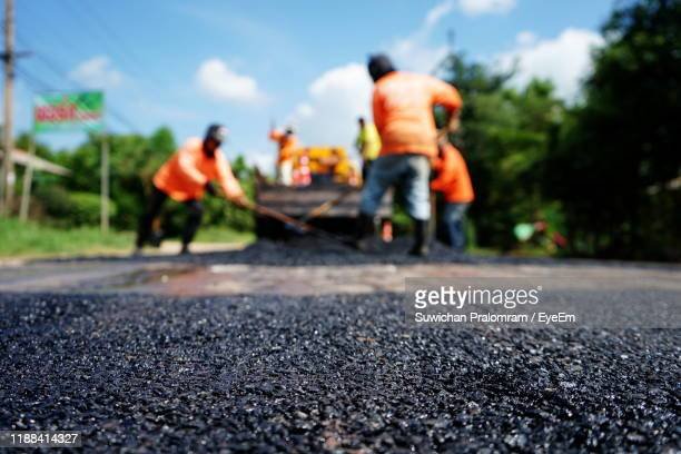 men working on road against sky - road construction stock pictures, royalty-free photos & images