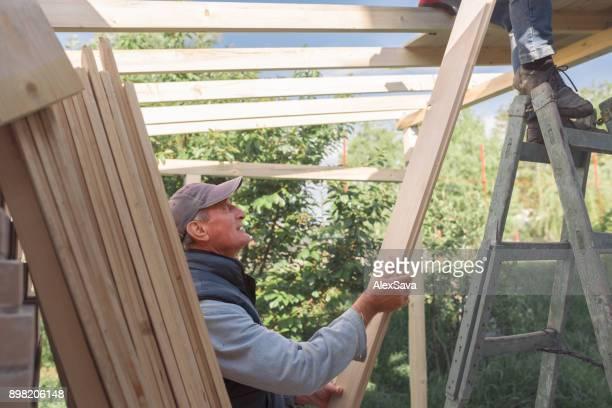 Men working together in building wooden chalet