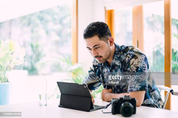 men working with a digital tablet - indonesian culture stock pictures, royalty-free photos & images