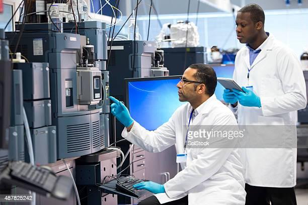 Männer arbeiten mit Specialist wissenschaftliche Ausstattung für Messen Chemikalien.