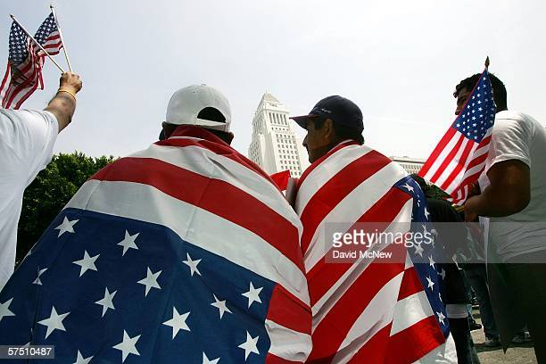 Men wrap themselves in American flags near City Hall during a march and rally on what is dubbed a Day Without Immigrants or the Great American...