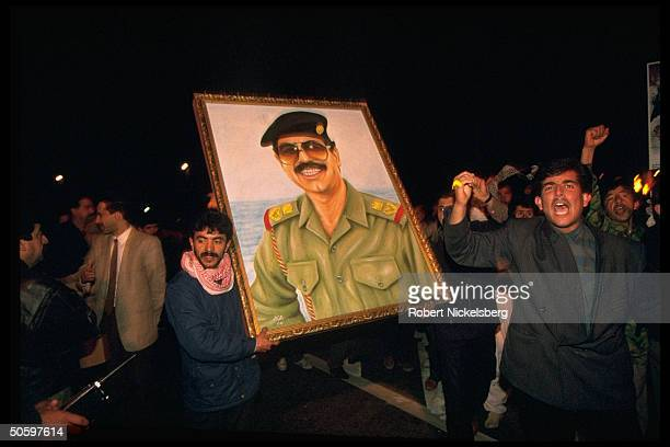 Men youths boys w poster imaging Pres Saddam Hussein in mil persona in night parade prob marking 3rd anniv of Gulf War