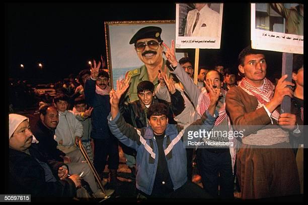 Men youths boys w poster imaging Pres Saddam Hussein in night parade prob marking 3rd anniv of Gulf War