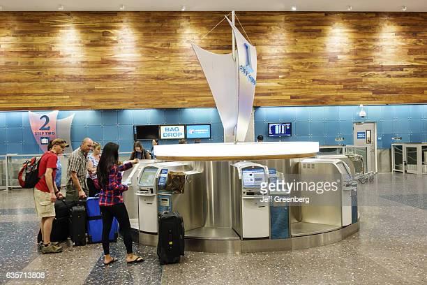 Mena dn women using the selfservice ticket machines at Honolulu International Airport