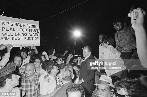 """Menachem Begin, Israeli leader of the Likud party, attends a rally in Tel Aviv. A demonstrator holds a sign reading, """"Kissinger: Your Plan for Peace..."""