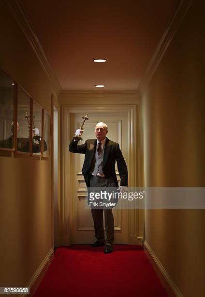 menacing butler in hallway - candlestick holder stock pictures, royalty-free photos & images