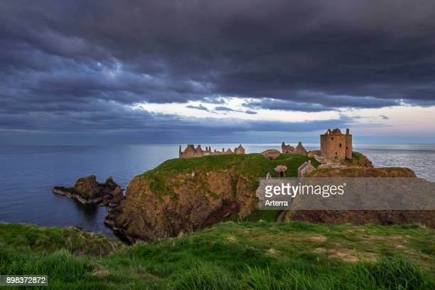 Menacing dark clouds above Dunnottar Castle, ruined medieval fortress near Stonehaven on cliff along the North Sea coast, Aberdeenshire, Scotland.