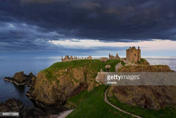 Menacing dark clouds above Dunnottar Castle ruined medieval fortress near Stonehaven on cliff along the North Sea coast Aberdeenshire Scotland