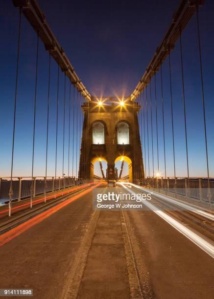 menai suspension bridge with traffic streaks - menai bridge stock photos and pictures