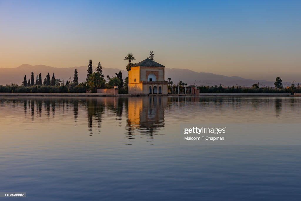 Menara Garden pavilion at sunrise, Marrakech, Morocco - with reflection in lake and view to Altas Mountains. : Stock Photo
