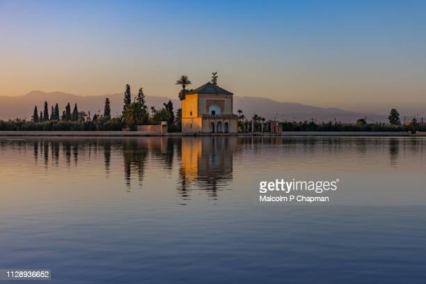 menara garden pavilion at sunrise, marrakech, morocco - with reflection in lake and view to altas mountains. - marruecos fotografías e imágenes de stock