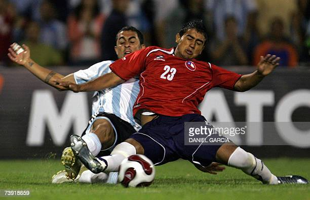 Argentine midfielder Daniel Montenegro vies for the ball with Chilean defender Arturo Vidal during the friendly football match at Malvinas Argentinas...