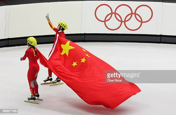 Meng Wang of China celebrates with Tianyu Fu of China as Fu was disqualified and Wang won gold in the women's 500m Short Track Speed Skating Final...
