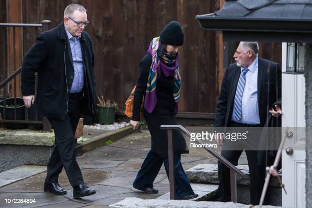 Meng Wanzhou, chief financial officer of Huawei Technologies Co., center, leaves her home under the supervision of security in Vancouver, British...