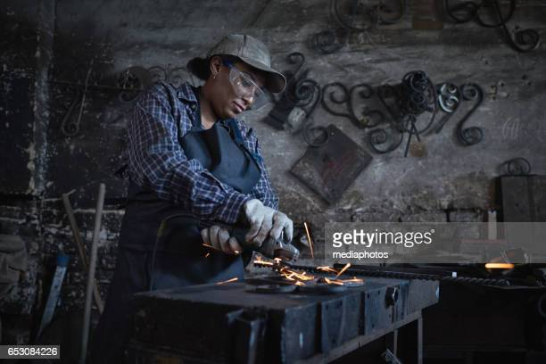 menial work - blacksmith shop stock photos and pictures