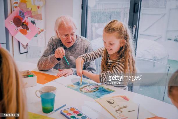 meningitis survivor painting on the dining room table with grandpa! - western europe stock pictures, royalty-free photos & images