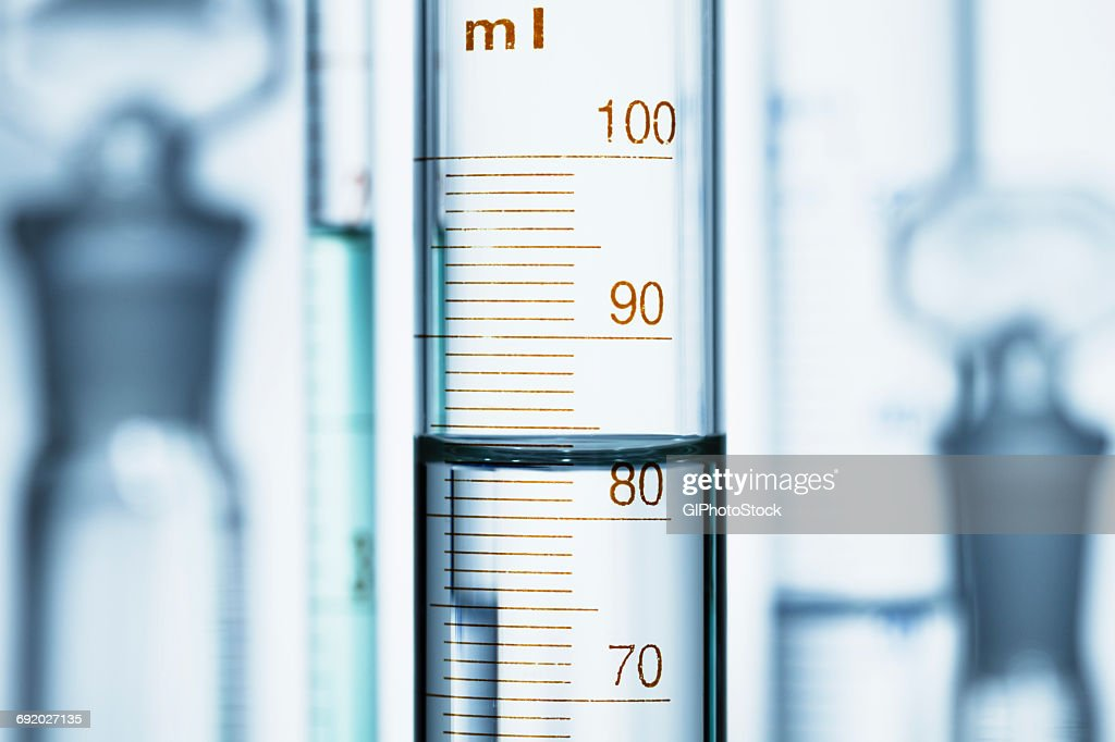 Meniscus. Curved surface (meniscus) of water in graduated cylinder. Liquid volume measured by reading the scale at the bottom of the meniscus. The reading is 82.6 mL : Stock Photo