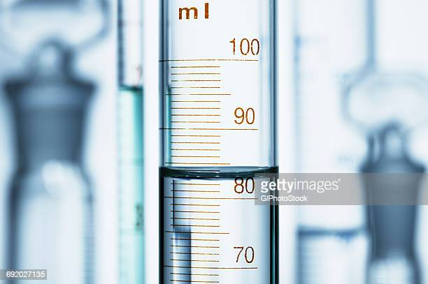 meniscus. curved surface (meniscus) of water in graduated cylinder. liquid volume measured by reading the scale at the bottom of the meniscus. the reading is 82.6 ml - cylinder stock pictures, royalty-free photos & images