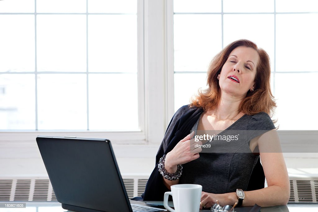 Menopausal woman having a hot flash at the office : Stock Photo