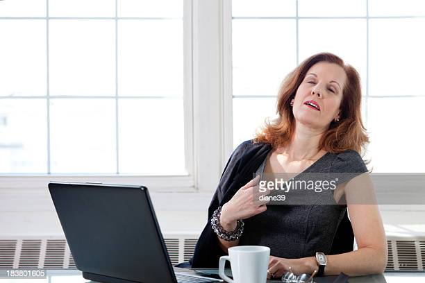 Menopausal woman having a hot flash at the office