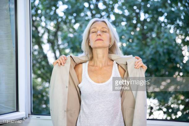 a menopausal woman having a hot flush. - menopause stock photos and pictures