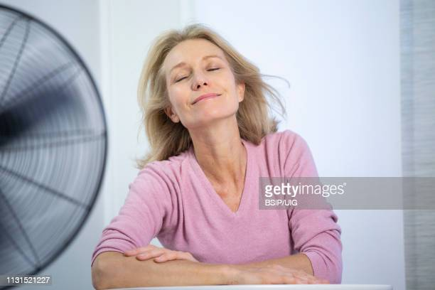 a menopausal woman having a hot flush. - menopause stock pictures, royalty-free photos & images