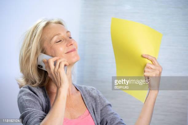 a menopausal woman having a hot flush. - värmebölja bildbanksfoton och bilder