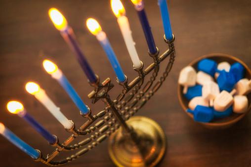 Menorah with burning candles and dreidel. Hanukkah preparations 629286860