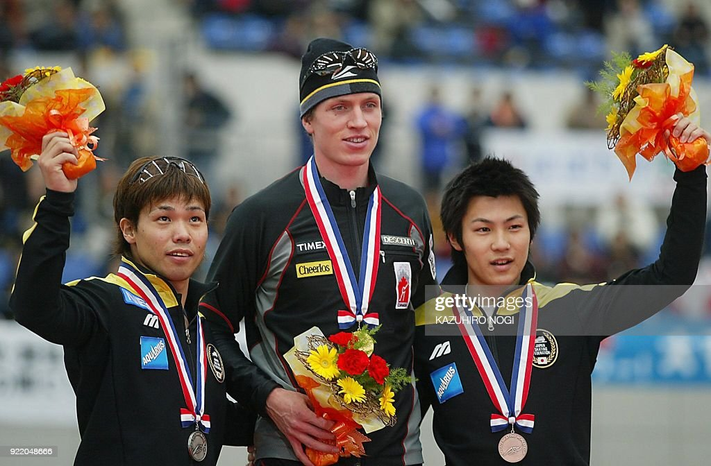 Men's 500m race winners, champion Jeremy Wotherspoon of Canada (C), second placer Hiroyasu Shimizu of Japan (L) and third placer Jojo Kato of Japan, celebrate at an award ceremony in the World Cup speed skating in Nagano, 07 December 2002. Wotherspoon won the event with a time of 35.19 seconds. AFP PHOTO/Kazuhiro NOGI / AFP PHOTO / Kazuhiro NOGI