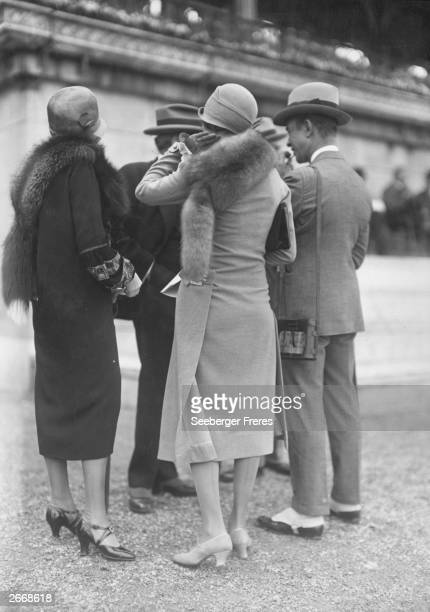 Men's and women's fashions from the mid1920s The two women wear tunic coats with fur stoles and cloche hats The men wear suits with slim lines and a...