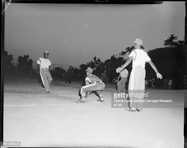 Men's baseball game at night with runner sliding into third base Pittsburgh Pennsylvania circa 19501970