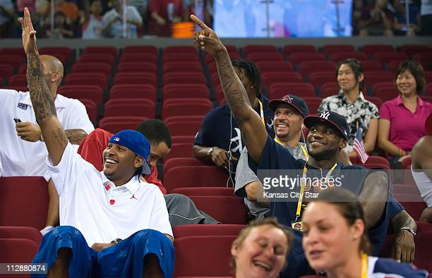 USA men's basketball players Carmelo Anthony and LeBron James right wave to cheering crowds during halftime as the USA women face the Czech Republic...