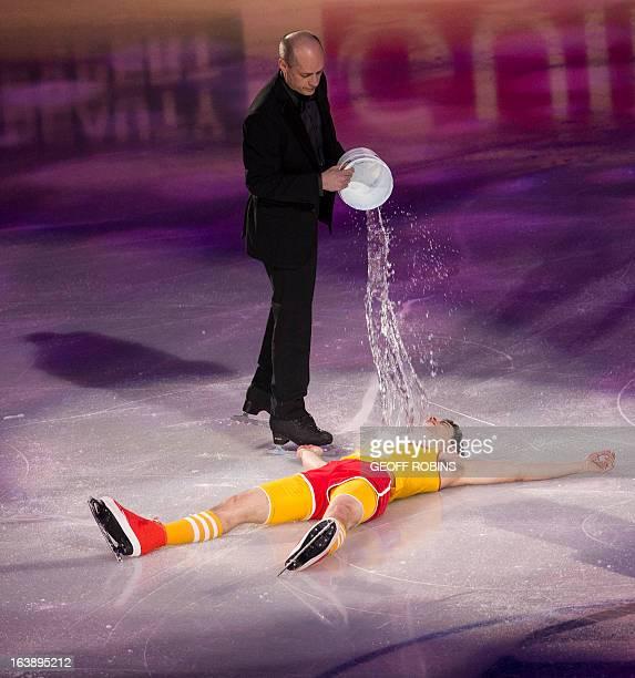 Men's bronze medalist Javier Fernandez of Spain has a bucket of water dumped on him by Canadian figure skating legend Kurt Browning during the 2013...
